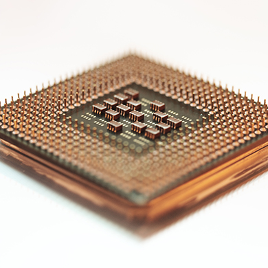 Close up view of a computer processor on a metallic reflective service. Shallow depth of field.