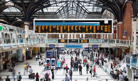 Busy railway station with digital signage