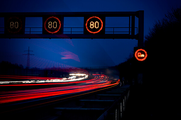Digital signage, Highway, Autobahn at dusk - traffic information system: Speed limit 80 km/h, no overtaking for trucks, long exposure