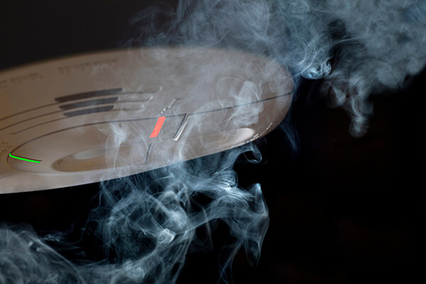 Smoke crawling over smoke detector.