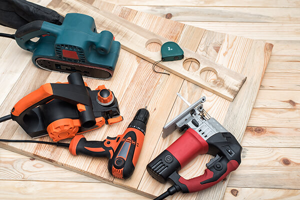 Set of handheld woodworking power tools for woodworking and workpiece lies on a light wooden background