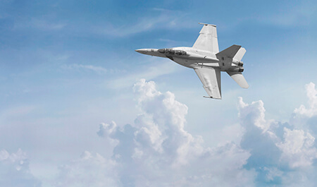 Panoramic view of an F-18 fighter jet cutting across the sky.
