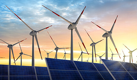 Power Conversion -Photovoltaic system and wind turbines in front of a sunrise morning sky